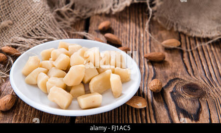 Raw Marzipan (close-up shot) with almonds on wooden background - Stock Photo