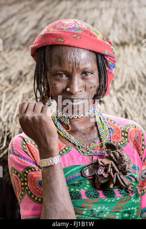 Portrait of a Mbororo woman with scars on her face and many good luck charms around her neck outside her hut. - Stock Photo