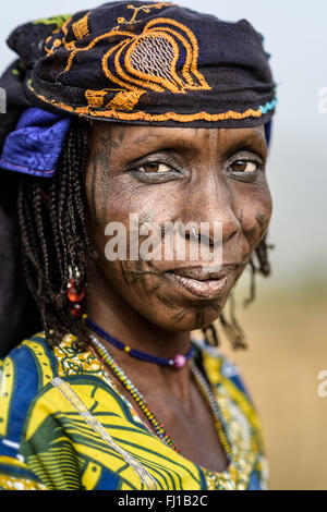 Portrait of a Mbororo woman from Cameroon with the typical scarification of this tribe on her face. - Stock Photo