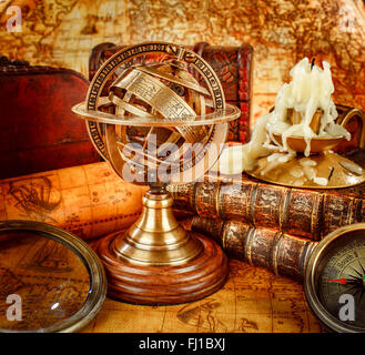 Vintage still life. Vintage old book and armillary sphere on an ancient world map in 1565. - Stock Photo