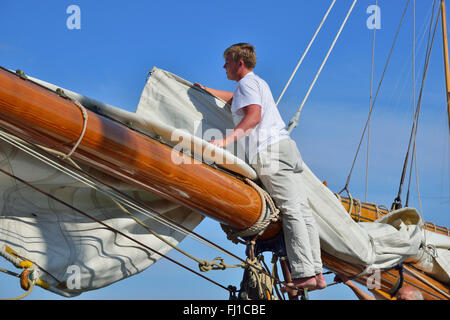 Crew of large wooden classic yacht furls the huge mainsail to the large wooden boom in Cowes Harbour, Cowes, Isle - Stock Photo