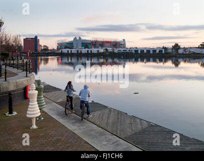 Two youths on bikes, a boy and a girl, view Old Trafford stadium, home of Manchester United Football Club, from - Stock Photo