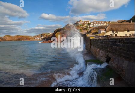 Waves crashing against the sea wall at Hope Cove, Devon, England - Stock Photo