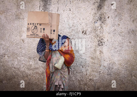 A woman beggar in the streets of Harar is hiding her face with a piece of cardboard and carrying her sleeping baby , Ethiopia Stock Photo