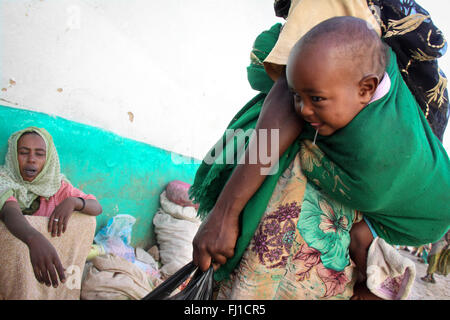 A woman carries her baby on her back in the market of Harar , Ethiopia - Stock Photo