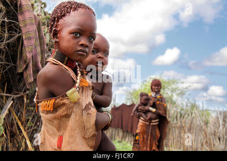 Portrait of hamer hamar young girl with her younger brother near Turmi, Omo valley , Ethiopia - Stock Photo