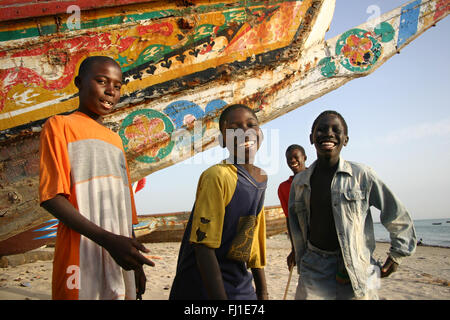Kids children posing on the beach of Joal Fadiouth , Senegal , in front of a traditional painted boat canoe - Stock Photo