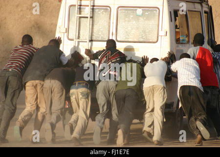 A group of black man are pushing together a broken down vehicle in Djenné , Mali - Stock Photo