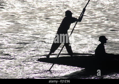 Two man are travelling on a boat in the harbor of Mopti, Mali - Backlight and  black and white picture - West Africa - Stock Photo