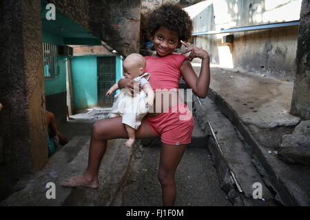 Girl with Baby Doll  living in favela de Rocinha, Rio de Janeiro, Brazil - Stock Photo