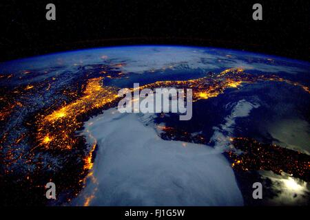 International Space Station view looking down at city lights over Italy and the European Alps from space January - Stock Photo