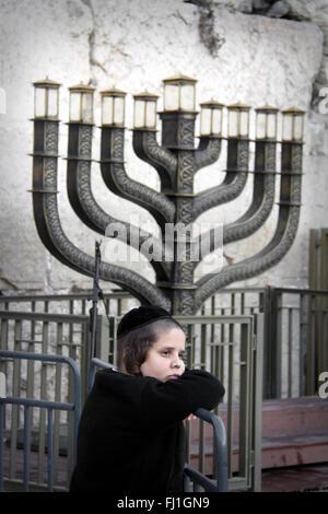 Jewish kid with kippa stands near a huge Menorah  at the Western Wall (Wailing Wall) of jerusalem , israel - Stock Photo