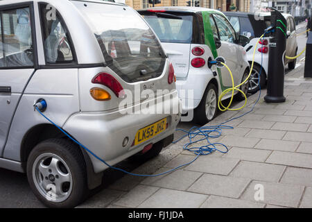 Electric vehicles plugged into charging points on a road in London, UK - Stock Photo
