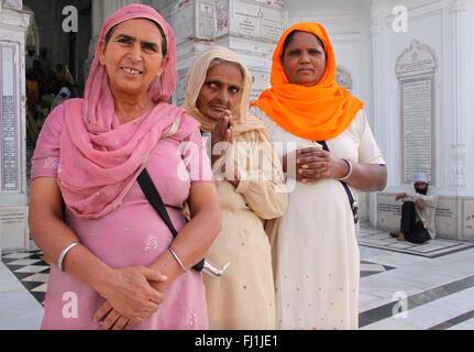 Sikh pilgrims  pray at the Golden temple, Amritsar , India - Stock Photo