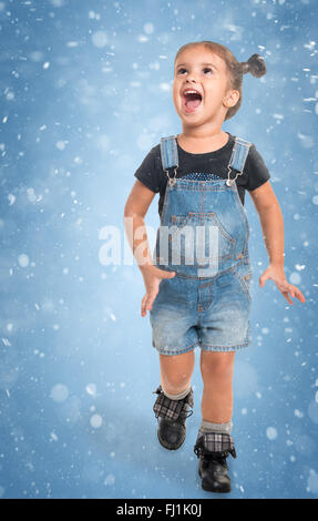 Cute little happy girl playing against  blue background with abstract snow - Stock Photo