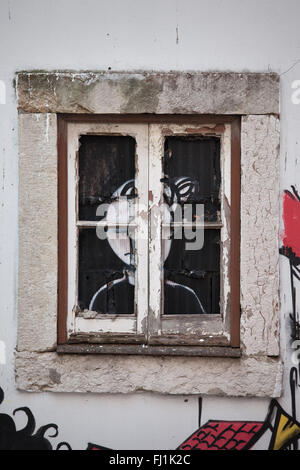 Sorrow concept, graffiti of a waiting woman by window with sad expression on face, Lisbon, Portugal - Stock Photo
