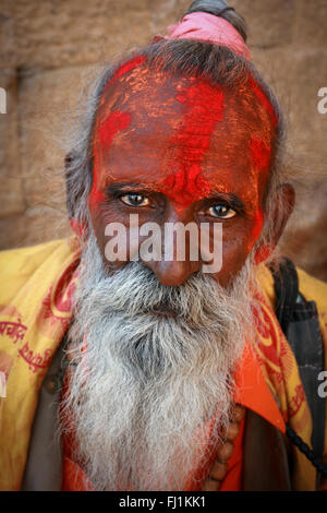Hindu holy man sadhu with face covered by red powder in Jaisalmer , India - Stock Photo