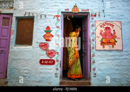 Woman in Jaisalmer fort with Ganesh painting, Rajasthan, India - Stock Photo