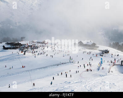 Overview of snow slopes busy with skiers at top of Le Grand Massif Express in Samoens Morillon ski area in French - Stock Photo