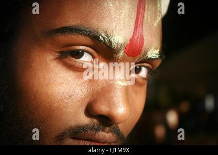 Eyes of Hindu man, face covered with powder and tilak - Bikaner , India - Stock Photo