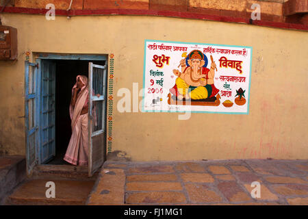 A woman stands at the entrance of a house in Jaisalmer fort, with painting of Hindu God Ganesh on the wall , Jaisalmer - Stock Photo