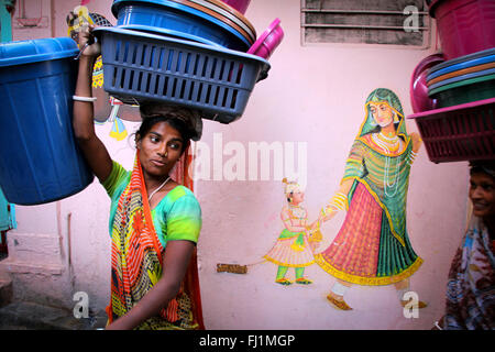 Woman  walk in a street of Udaipur, carrying basket on her head, painting of a woman with kid on the wall, Rajasthan, - Stock Photo