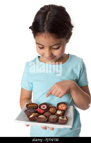 Little girl pointing at a chocolate bonbon on white background - Stock Photo