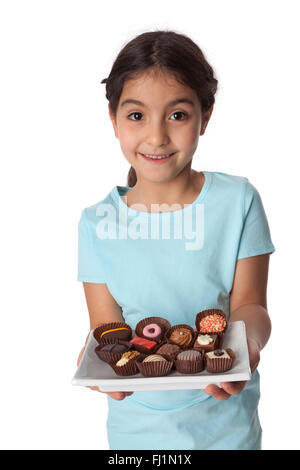 Little girl holding a plate of chocolate bonbons on white background - Stock Photo