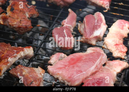 Barbecuing meat on charcoal fire closeup image. - Stock Photo