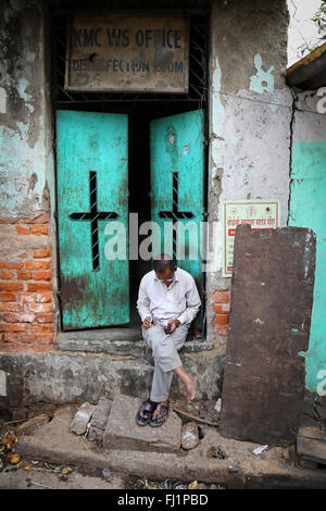 Man reading in a street of Kolkata with open green door behind hiù - Stock Photo
