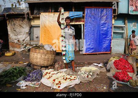 Flower seller at the Kolkata Mullick ghat flower market , India - Stock Photo