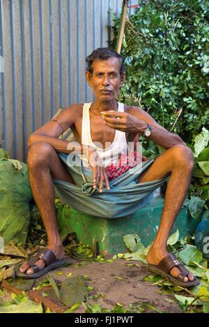 Flower seller drinking tea chaï at Mullick ghat flower market in Kolkata , India - Stock Photo