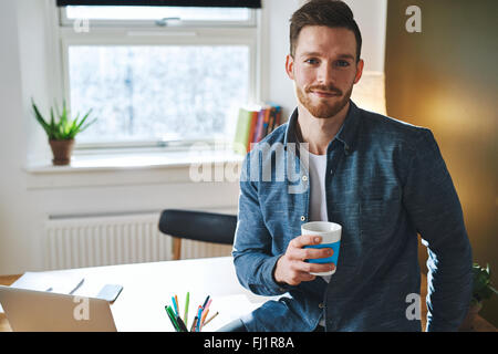 Confident young entrepreneur sitting in his office at the desk looking into the camera - Stock Photo