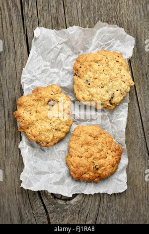 Oats cookies on baking paper over wooden background, top view - Stock Photo