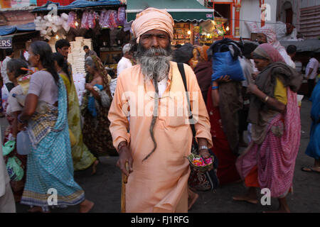Saddhu stands in the crowd during Kumbh mela in haridwar , India - Stock Photo
