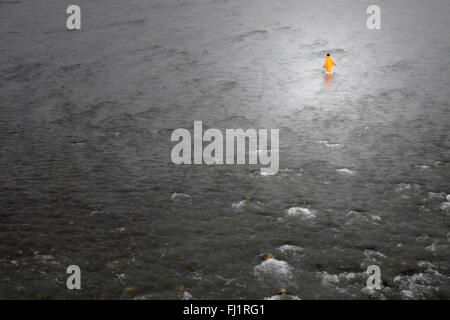 man with saffron dress walks alone in the water of the ganges during Kumbh mela, Haridwar - Stock Photo
