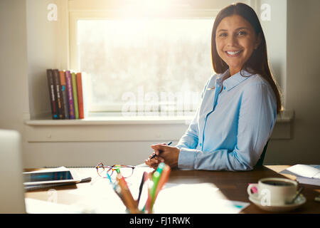 Successful business woman sitting at her desk in a office smiling at the camera - Stock Photo
