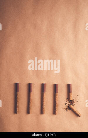 Quit smoking concept, flat lay arranged cigarettes with broken one at the end as final decision to quit is made - Stock Photo