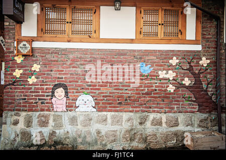 A new mural on a brick wall representing the face of a for Mural village seoul
