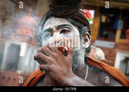 Sadhu holy man smoking chillum in  Varanasi, India - Stock Photo