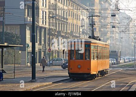 Old vintage orange tram on the street of Milan, Italy - Stock Photo