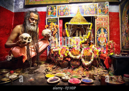 Portrait of Aghori cannibal sadhu holy man in front of decorated temple in Varanasi, India - Stock Photo
