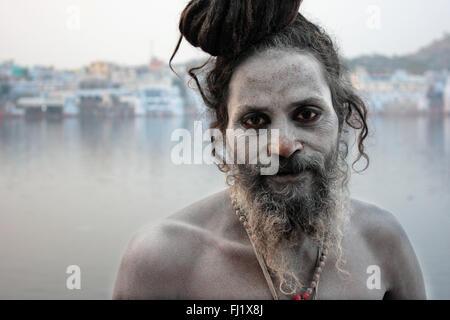 Naga sadhu holy man in front of the holy lake of  Pushkar, Rajasthan - Stock Photo