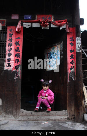 Chinese girl sitting at the entrance of her house in Shiqiao village, Guizhou, China - Stock Photo