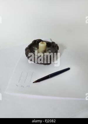candle, feather pen on the stack of paper with inscriptions - Stock Photo