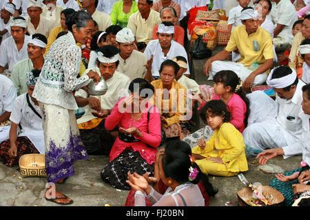 Hindu Balinese people praying during Kuningan ceremony in Ubud, Bali , Indonesia - Stock Photo