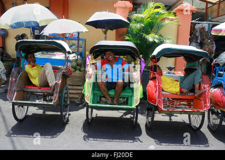 Becak drivers in a street of Yogyakarta , Indonesia - Stock Photo