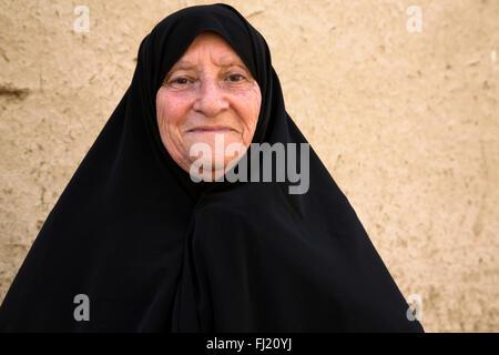 Portrait of old Iranian woman covered with traditonal black hijab islamic veil in Yazd, Iran - Stock Photo