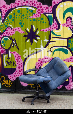 Broken Chair in front of a wall of Graffiti London - Stock Photo