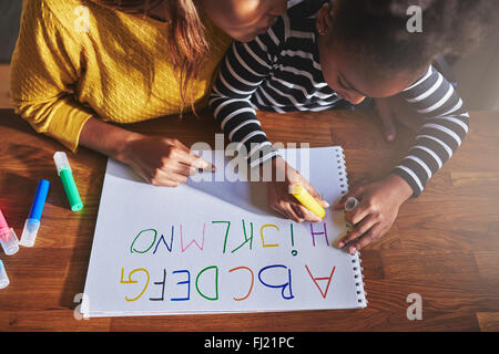 Overhead view of little girl learning the alphabet using coloured crayons - Stock Photo